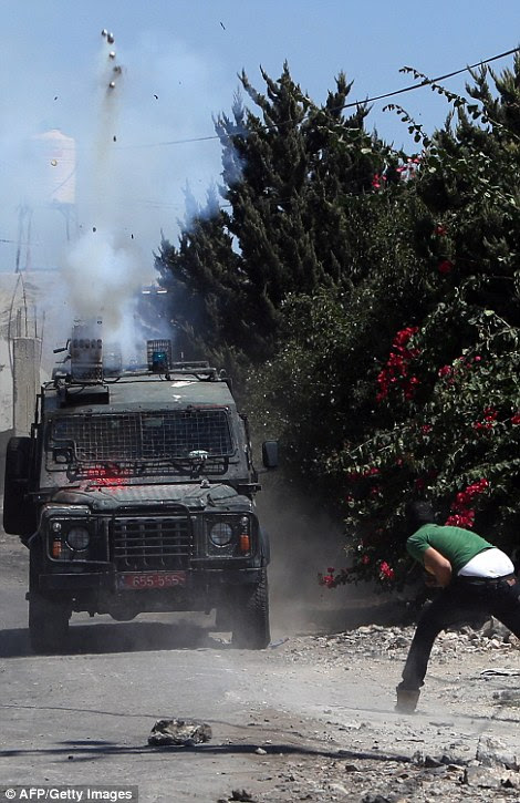 A Palestinian protester throws stones towards a vehicle of Israeli security forces firing tear gas canisters during clashes following a demonstration against the expropriation of Palestinian land by Israel on August 28, 2015 in the village of Kafr Qaddum, near Nablus in the occupied West Bank