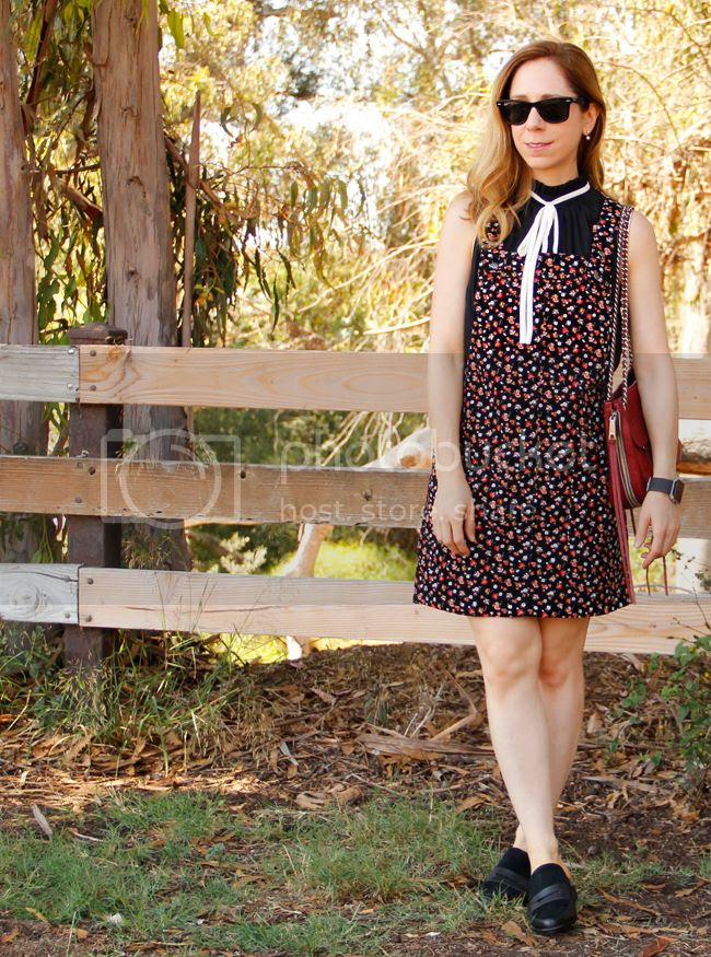 Southern California fashion blogger The Key To Chic wears a Who What Wear tie neck blouse with a floral overall dress and Rebecca Minkoff Swing bag.