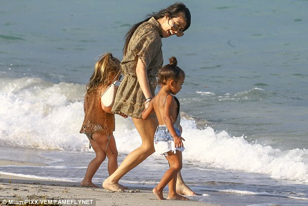 Splish splash:At first, the two-year-old seemed to prefer the sand but Kourtney stepped in, walking the toddler and Penelope down to the water's edge