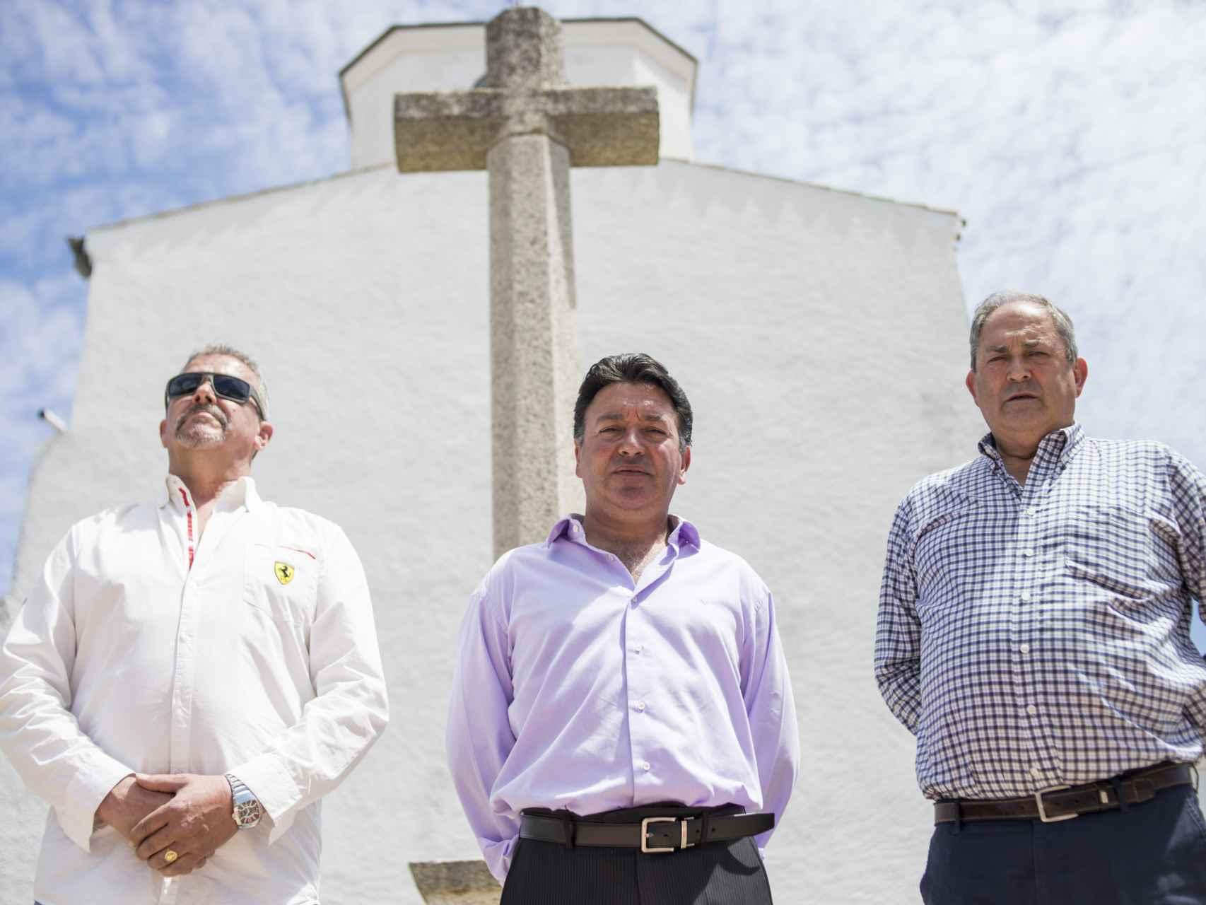 El alcalde (centro) con dos vecinos del pueblo frente a la cruz que emula a la del Valle de los Caídos y frente a la  cual pretenden enterrar al dictador.