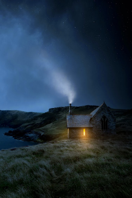 rosiesdreams:  Somewhere ..  Photo by David Soar  I love this picture. It brings many images to mind. An isolated cabin somewhere on a rise of land near a small body of water. Darkness is surrounding the cabin but there's a light inside. Smoke is drifting upward from the chimney. Someone is home. Who lives there? Why would someone want to live far from the madding crowd? Does the person ever feel lonely? I don't see a car. How does this person travel? I want to peek into the window. Should I?