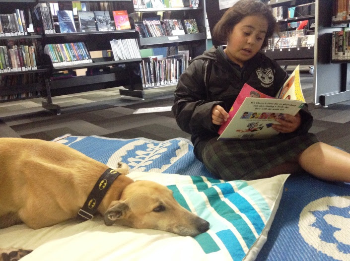 A girl reads to a dog.