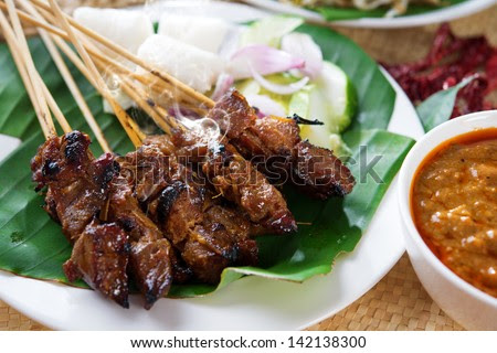 Satay or sate, skewered and grilled meat, served with peanut sauce, cucumber and ketupat. Traditional Malay food. Delicious hot and spicy Malaysian dish, Asian cuisine. - stock photo
