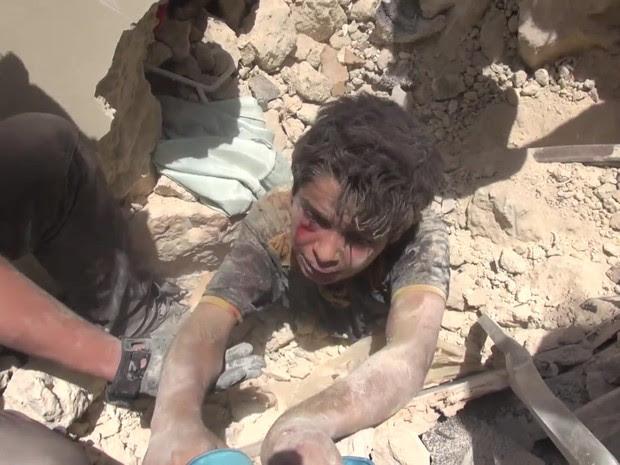 Equipes de resgate correram contra o tempo para resgatar um menino sob escombros após um bombardeio em Aleppo (Foto: BBC)