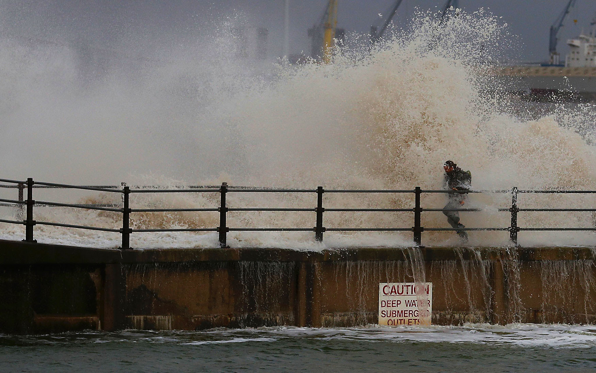 A man is battered by a wave as he walks along the seafront in New Brighton, northern England November 16, 2016.