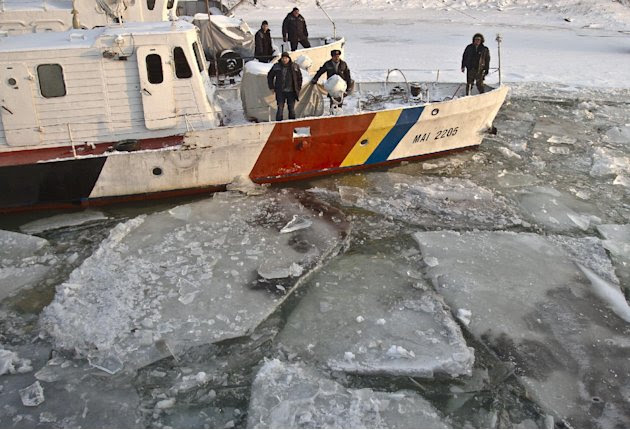 The crew of a border patrol ship waits as their boat is freed from frozen Danube waters by an ice breaker, in Giurgiu, southern Romania, Wednesday, Feb. 8, 2012.  Bulgaria and Romania are suspending a