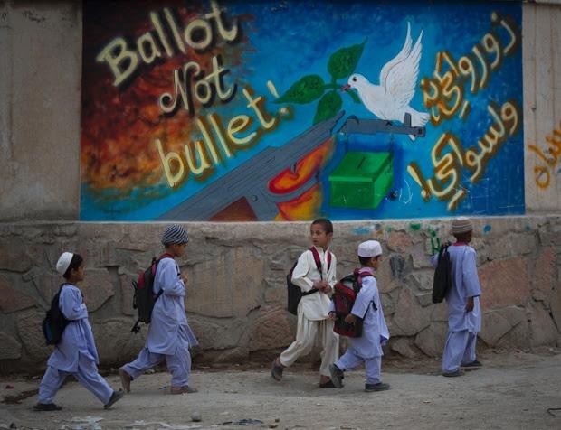 Schoolchildren walk past election graffiti on their way home on the outskirts of Kandahar