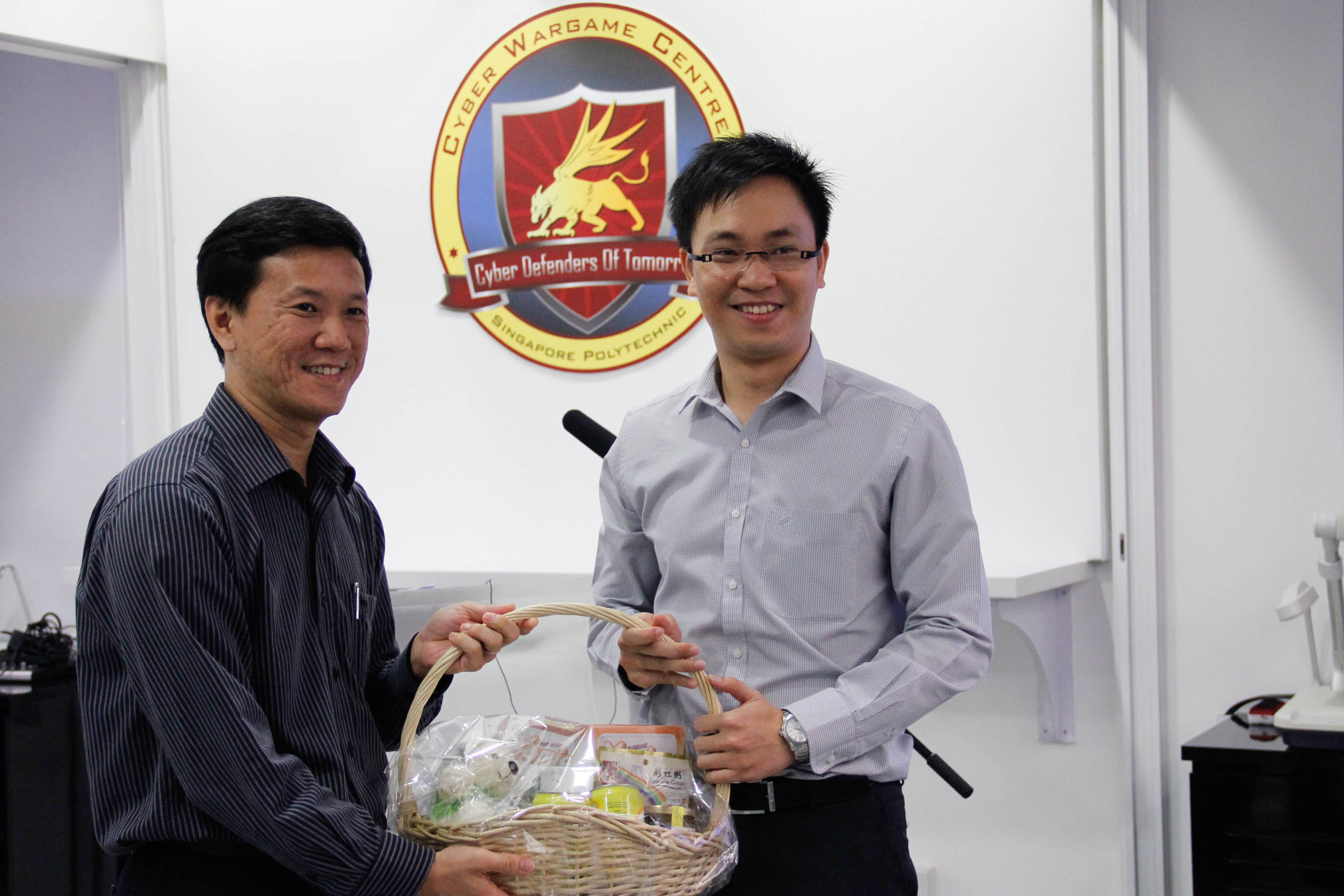 Mr Liew presenting a home-made SP gift hamper  to Mr Huynh