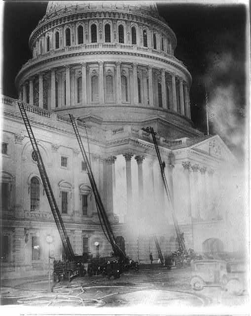 View of the U.S. Capitol during the fire which destroyed the studio of Artist Chas. Moberly & considerably damaged the House Document Room - fire engines with ladders going up the side of the Capitol