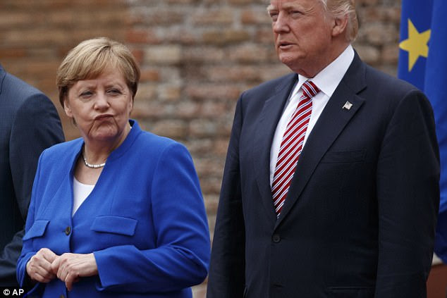 Angela Merkel looks on as she is stood next to Donald Trump while waiting to have a photograph taken on Friday as part of the G7 meeting