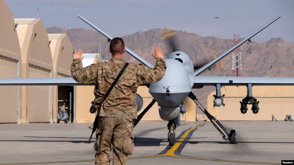 បុរសជើងអាកាសអាមេរិកម្នាក់ដឹកនាំកងកម្លាំងផ្លូវអាកាសតាមយន្តហោះដ្រូន MQ-9 Reaper ពេលដែលយន្តហោះនោះនៅលើផ្លូវវាលយន្តហោះទៅកាន់ទីលានអាកាស Kandahar ប្រទេសអាហ្វហ្គានីស្ថានាខែមីនាកន្លងទៅនេះ។