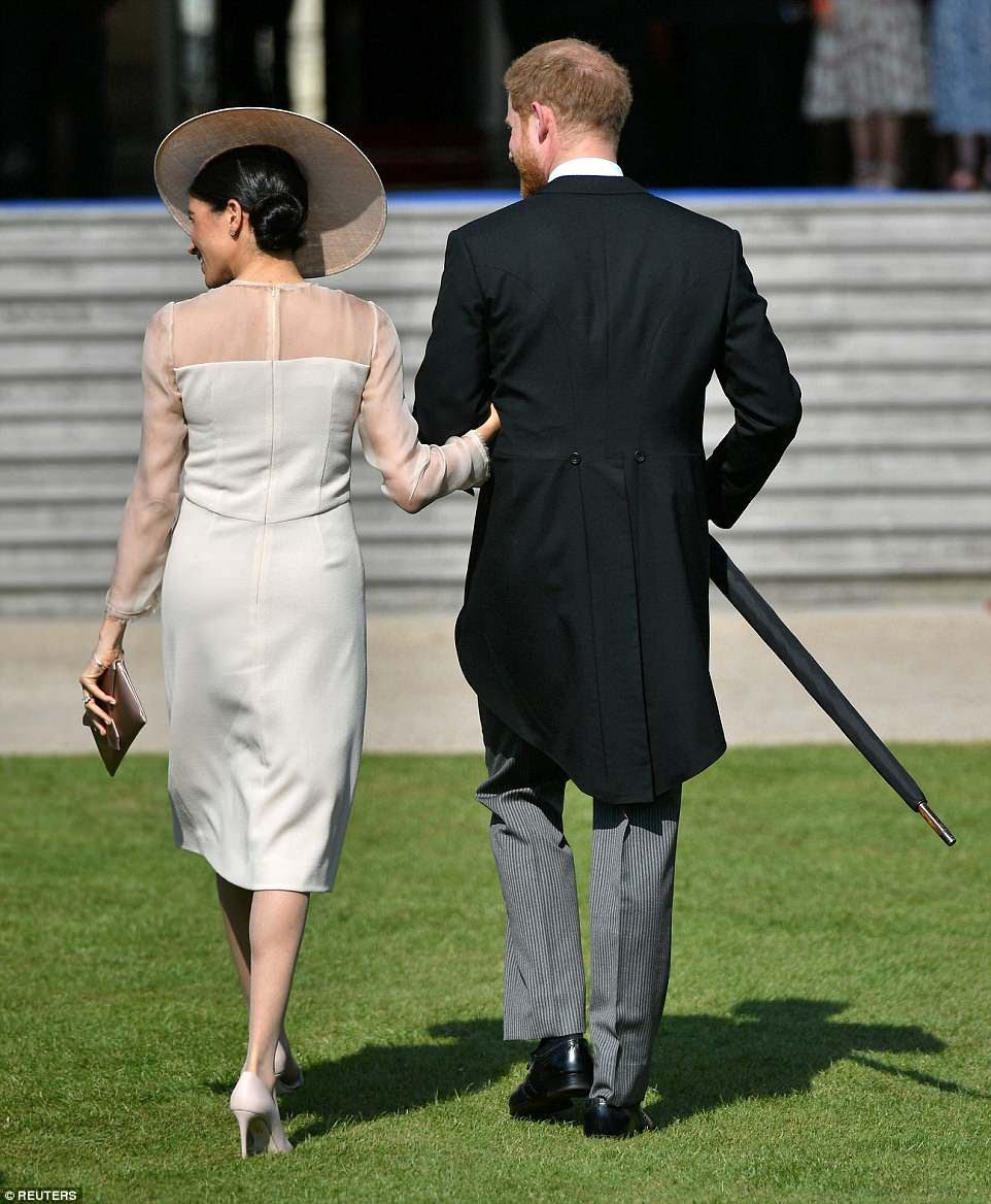 The pair never seemed to lose touch with one another, and Meghan held her new husband's arm as she navigated the grass in 4.5-inch heels