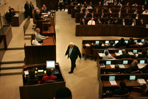 """FILE - In this Monday, Oct. 31, 2005 file photo, Israeli Prime Minister Ariel Sharon walks before delivering a speech at the opening of the winter session of the Knesset, Israel's parliament, in Jerusalem. The son of former Israeli Prime Minister Ariel Sharon says his father has died on Saturday, Jan. 11, 2014. The 85-year-old Sharon had been in a coma since a debilitating stroke eight years ago. His son Gilad Sharon said: """"He has gone. He went when he decided to go.""""  (AP Photo/Oded Balilty, File)"""