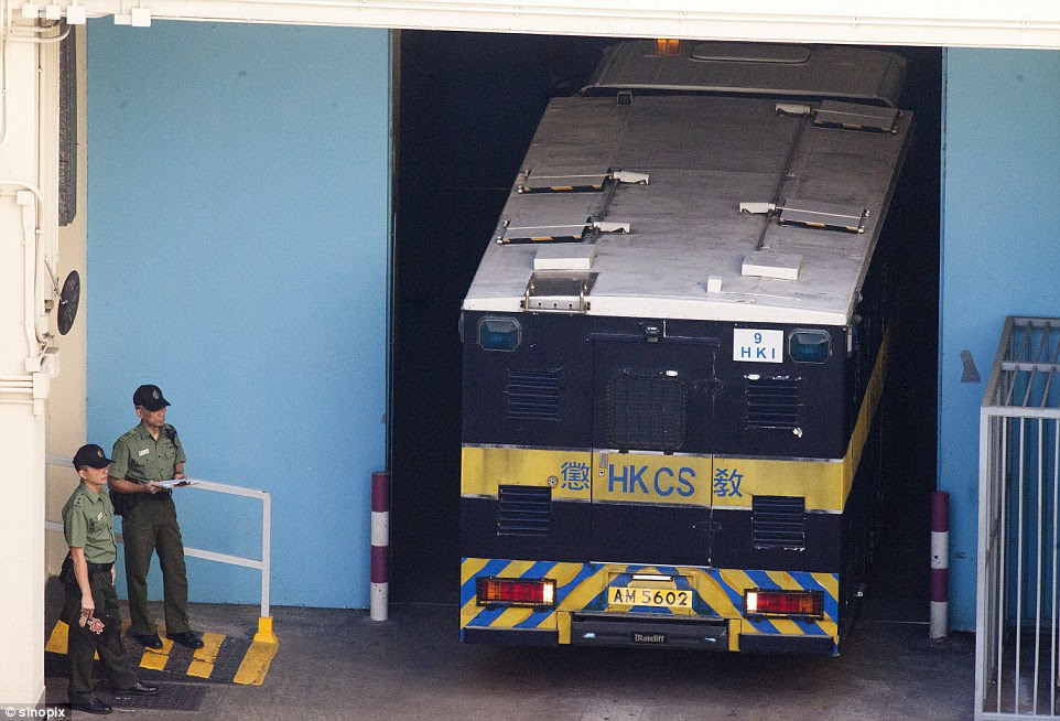 High security: Prison guards look on as a high security prison van reverses into a courtyard at the Lai Chi Kok Reception Centre to take British ex-banker Rurik Jutting to his trial at the High Court of Hong Kong