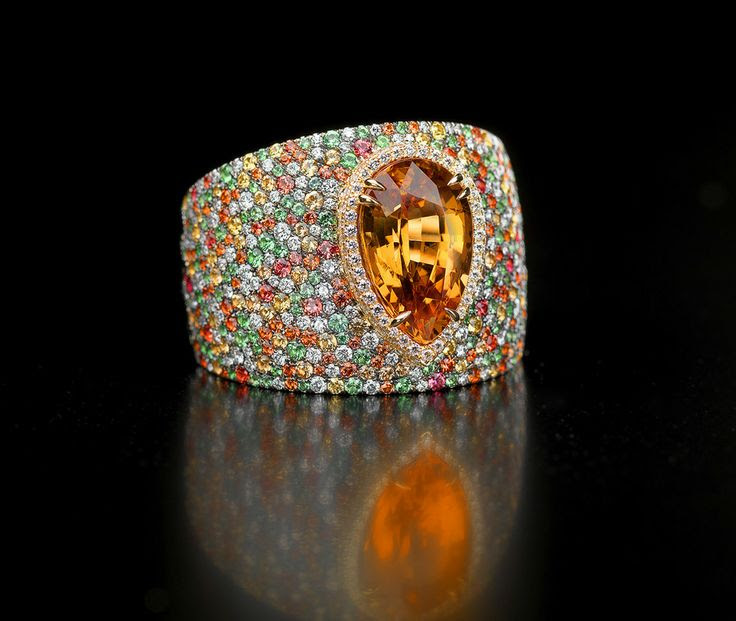 Tutti Frutti Mandarin Garnet ring    The 5.89 carat pear shape Mandarine garnet at the center is surrounded by a combination of yellow sapphires, mandarine garnets, tsavorites, and diamonds  that give the impression a spring garden of gems. 597 stones are set to create this stunning burst of color and workmanship.