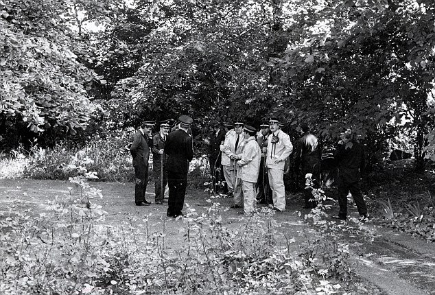 Police are pictured searching the grounds of a property where the body of Marguerite Walls