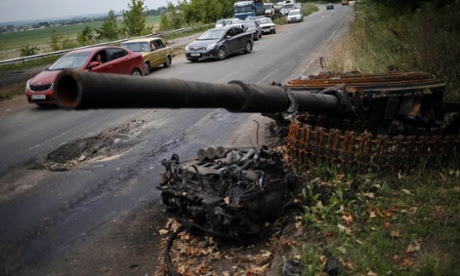 Cars drive past the remains of a destroyed pro-Russian separatist tank near a Ukrainian army checkpoint just outside the eastern Ukrainian town of Kramatorsk.