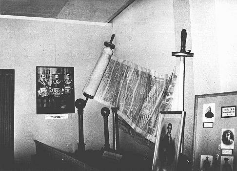 "A display, entitled ""British Freemasonry,"" at an antisemitic and anti-Masonic exhibition in Berlin: the juxtaposition of a Torah scroll and a picture of King Edward bearing Masonic regalia. Berlin, Germany, March 7, 1941."