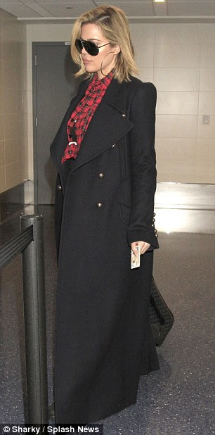 A chic addition: Choosing to keep a hint of a smart and chic vibe, the TV show host donned a black overcoat to keep any chills at bay - something she was forced to ditch in the name of airport security checks