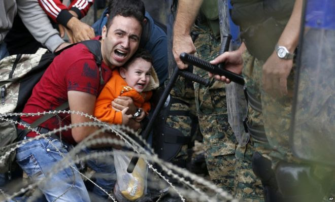 A migrant man holding a boy react as they are stuck between Macedonian riot police officers and migrants during a clash near the border train station of Idomeni, northern Greece, as they wait to be allowed by the Macedonian police to cross the border from Greece to Macedonia, Friday, 21 August 2015