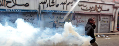 An Egyptian anti-government activist runs to throw back a tear gas canister fired by riot police officers during clashes in Cairo, Egypt, Friday, Jan. 28, 2011 (AP Photo/Lefteris Pitarakis)