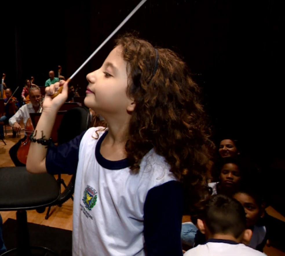 Isabela Lira, de 8 anos, regeu a orquestra ao lado do maestro (Foto: Toni Mendes/EPTV)