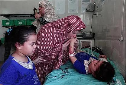 Enfant blessé en grève de la fusée sur aire de jeux dans le camp de réfugiés de Shati