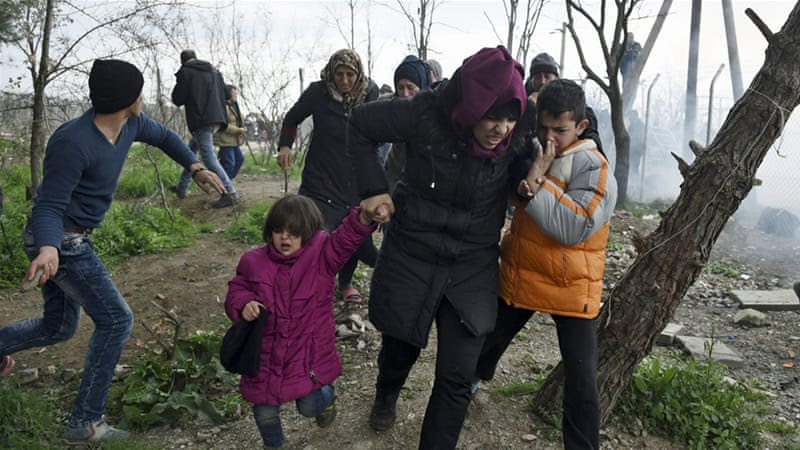 A woman holds her children as they run away after Macedonian police fired tear gas [Giannis Papanikos/AP]