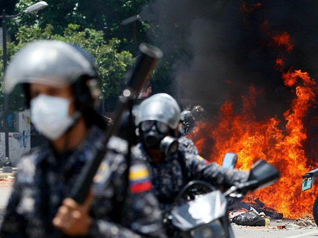Venezuelan Bolivarian National police move away from the flames after an explosion at Altamira square during clashes against anti-government demonstrators in Caracas, Venezuela, Sunday, July 30, 2017. The explosion injured several officers and damaged several of their motorcycles. The officers were then seen throwing several privately owned motorcycles into the remaining fire in reprisal. (AP Photo/Ariana Cubillos)