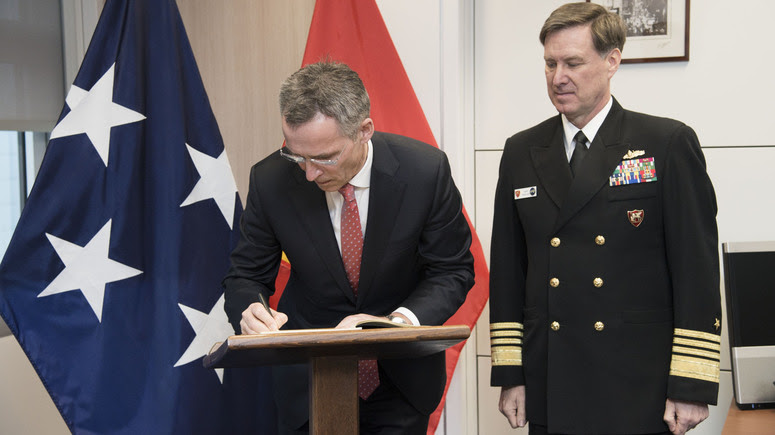 NATO Secretary General Jens Stoltenberg sings the Book of Honour of the Allied Joint Force Command, Naples in the presence of JFC Commander Admiral Mark Ferguson