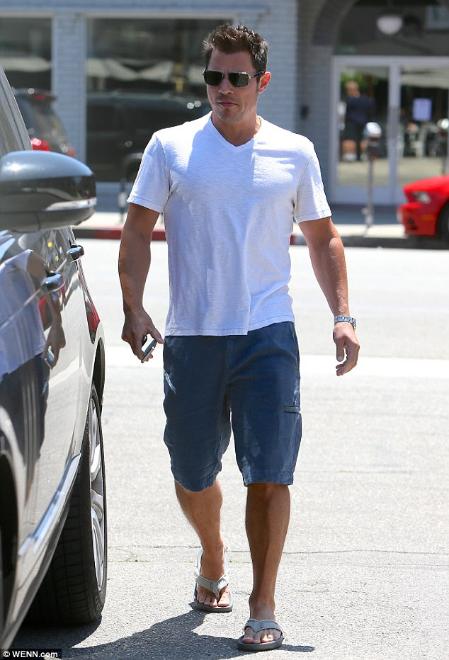 Dad duds: Father-to-be wore a very casual look of blue cargo shirts with a white V-neck T-shirt and flip flops