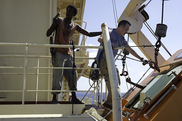 Tom Hanks as Captain Phillips is pushed into a lifeboat by a gun-toting pirate in a scene from the film