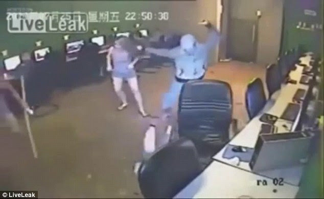 Ruthless: All the while one of the attackers was dragging a young woman around the internet café. In the background, other customers can clearly be seen looking at their screens without trying to help or escape