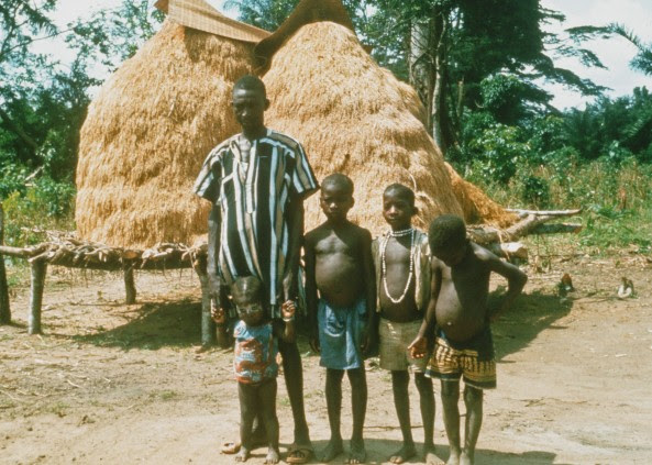 After a day of teaching at Gboveh High School, I would follow jungle trails to surrounding villages and farms. This picture features a Kpelle farmer with his three boys and young daughter. Harvested rice is piled behind the family.