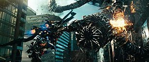 In a city full of skyscrapers, a robot wearing jet thrusters on his back holding a cannon flies toward a large snake-like robot. A tentacle of the larger robot is exploding.