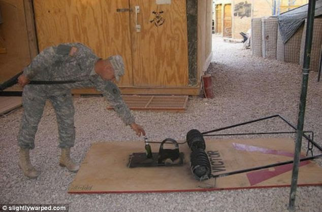 Mousetrap: A soldier tests out this homemade giant vermin catcher with a bottle of beer at an army base