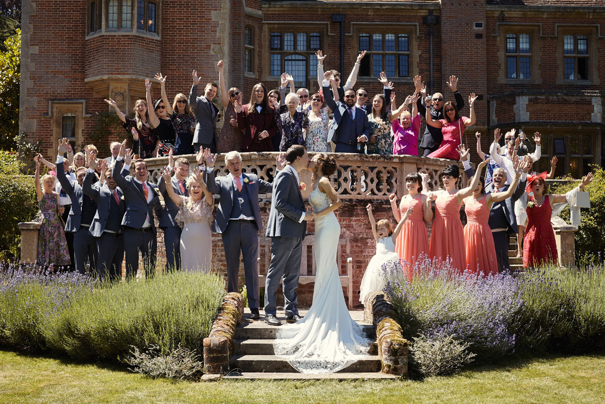 Entire Wedding Party and guests group photo on steps in the gardens at Lanwades Hall Wedding Photos - helloromancephotography.com