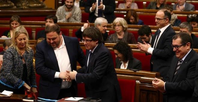 El presidente de la Generalitat, Carles Puigdemont (c), felicita al vicepresidente y conseller de Economía, Oriol Junqueras (i) el pasado día 20 en el Parlament. /EFE