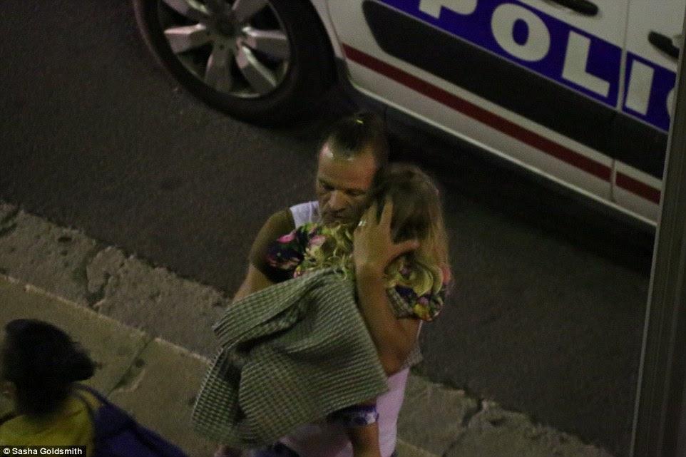 Um homem que prende uma menina pequena realizado o jovem traumatizada longe da cena do massacre em Nice, sul da França