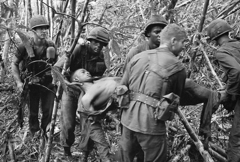Description of  Soldiers of the 101st Airborne Division carry a wounded buddy through the jungle in May 1966. (AP Photo/Henri Huet)