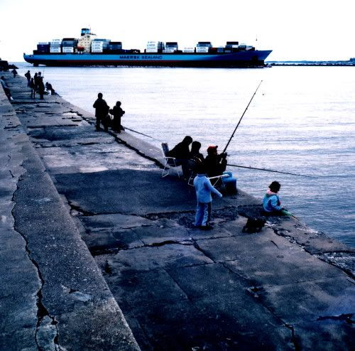 A large container ship enters port while families watch