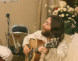 A bearded, bespectacled man in his late twenties, with long dark brown hair and wearing a loose-fitting pajama shirt, sings and plays an acoustic guitar. White flowers are visible behind and to the right of him.