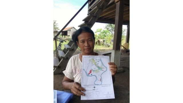 Village head Srang Lanh holds a map of the new village of Kbal Romeas, where 52 families who rejected the government's resettlement deal have opted to live (Image: Sangeetha Amarthalingam)