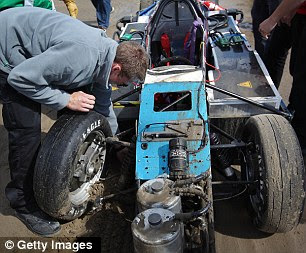 A mechanic removes the broken wheel from the car