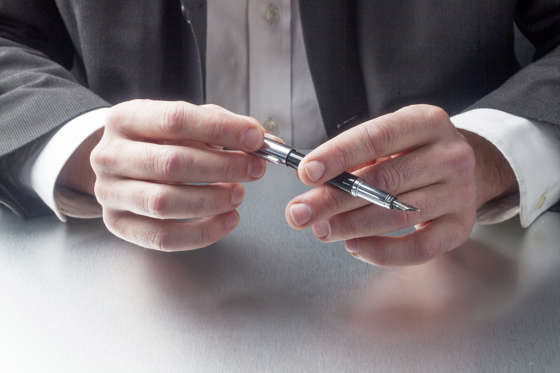 Man holding a ink pen at the office.