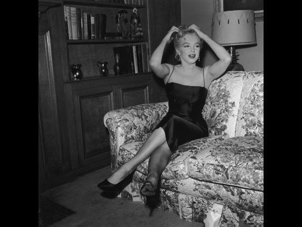 Monroe sits on a couch and adjusts her hair in front of a bookshelf. She wears a black evening dress and heels.