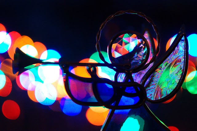 A colorful glass angel with lights in the background.