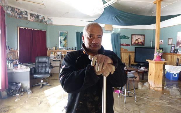 James Takarangi mops out his Waitotara home. Wanganui flood.