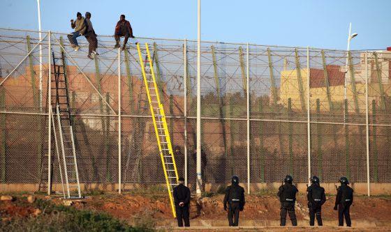 Inmigrantes encaramados a la valla de Melilla.