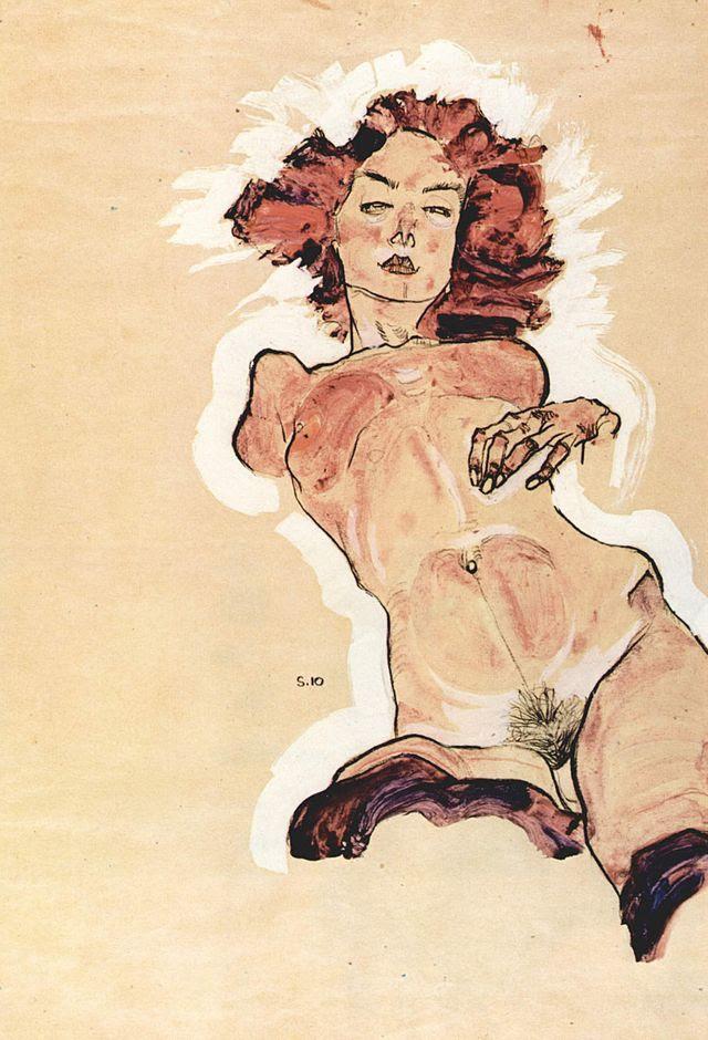 Reprodução da obra Nu feminino, do artista Egon Schiele, de 44,3 x 30,6 cm, feita em 1910, com tintas idiana, tempera e aquarela sobre papel. Trata-se de uma mulher nua de cabelos ruivos revoltos, com o corpo ligeiramente inclinado para a esquerda, sem braços, com uma mão solta sobre o peito esquerdo e pelos pubianos pretos. Parece que a mulehr teve parte dos membros inferiores decepdada. O corpo é em tom bege mesclado com tom avermelhado na área dos seios e do abdômen.